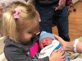 Une petite fille surprise par le bébé qui pleure